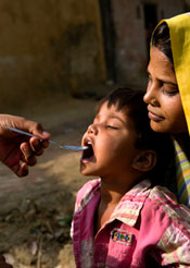 Mother holding child receiving medication.